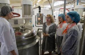 Главный технолог производства рассказывает Елене Паниной и школьникам процесс приготовления косметического крема